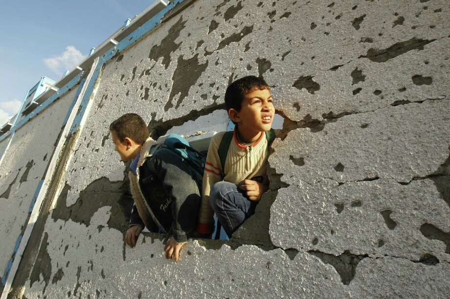 Palestinian schoolboys look through a hole at their damaged U.N.-run school in Gaza City, on November 24, 2012. Photo: MOHAMMED ABED, AFP/Getty Images / AFP