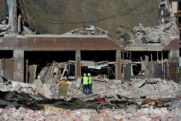 Inspectors stand in debris, Saturday, Nov. 24, 2012, at the site of a gas explosion that leveled a strip club in Springfield, Mass., on Friday evening. Investigators were trying to figure out what caused the blast where the multistory brick building housing Scores Gentleman's Club once stood. (AP Photo/Jessica Hill) Photo: Jessica Hill