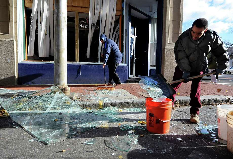Robert Spano, left, and Alan Hugley clean up broken glass, Saturday, Nov. 24, 2012, outside of Punta cana Restaurant & Bar, a few blocks from the site of a Friday-evening gas explosion that leveled a strip club in Springfield, Mass. (AP Photo/Jessica Hill) Photo: Jessica Hill