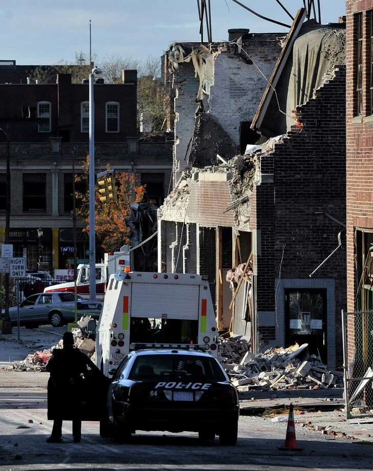 People keep a perimeter, Saturday, Nov. 24, 2012, around the area where a gas explosion leveled a strip club in Springfield, Mass., on Friday evening. Investigators were trying to figure out what caused the blast where the multistory brick building housing Scores Gentleman's Club once stood. (AP Photo/Jessica Hill) Photo: Jessica Hill