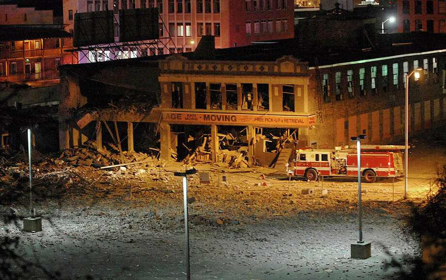 A firetruck is parked next to a damaged building after a nearby gas explosion leveled another building in downtown Springfield, Mass. on Friday, Nov. 23, 2012. (AP Photo/Springfield Republican, David Molnar) Photo: David Molnar