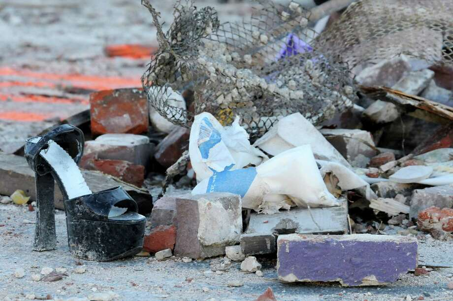 Items from the Score's Gentleman's Club are seen in the rubble on Saturday, Nov. 24, 2012, the morning after Friday night's explosion in Springfield, Mass. Dozens of building inspectors began assessing homes and businesses in Springfield on Saturday, a day after a natural gas explosion leveled the Scores Gentleman's Club located next to a day care and heavily damaged a dozen other structures.  (AP Photo/The Republican, Dave Roback) Photo: Dave Roback