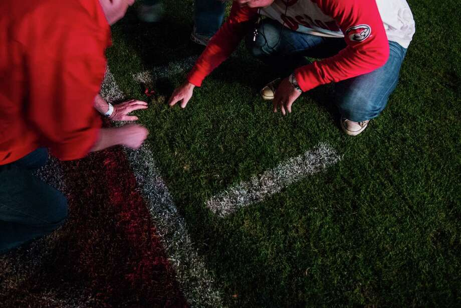 Long after the lights went out, former players dig up souvenier chunks of turf at Robertson Stadium following a college football game against Tulane on Saturday, Nov. 24, 2012, in Houston. Photo: Smiley N. Pool, Houston Chronicle / © 2012  Houston Chronicle