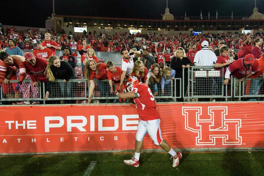 Houston defensive lineman Ameen Behbahani (93) high-fives fans after defeating Tulane in a college football game at Robertson Stadium, Saturday, Nov. 24, 2012, in Houston. Houston won the game 40-17. Photo: Smiley N. Pool, Houston Chronicle / © 2012  Houston Chronicle