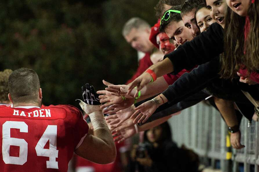 Houston offensive linesman Ty Cloud (64) high-fives fans after defeating Tulane in a college footbal