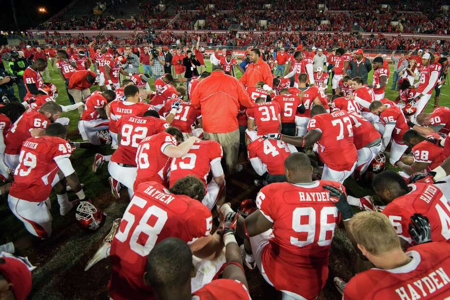 Houston players kneel in prayer at midfield after defeating Tulane in a college football game at Robertson Stadium, Saturday, Nov. 24, 2012, in Houston. Houston won the game 40-17. Photo: Smiley N. Pool, Houston Chronicle / © 2012  Houston Chronicle
