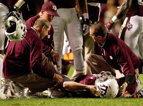 Texas A&M quarterback Johnny Manziel (2) is looked over by the Texas A&M trainers after he was hurt on a running play during the first quarter of a NCAA football game, Saturday, Nov. 24, 2012, in Kyle Field in College Station. Photo: Nick De La Torre, Houston Chronicle / © 2012  Houston Chronicle