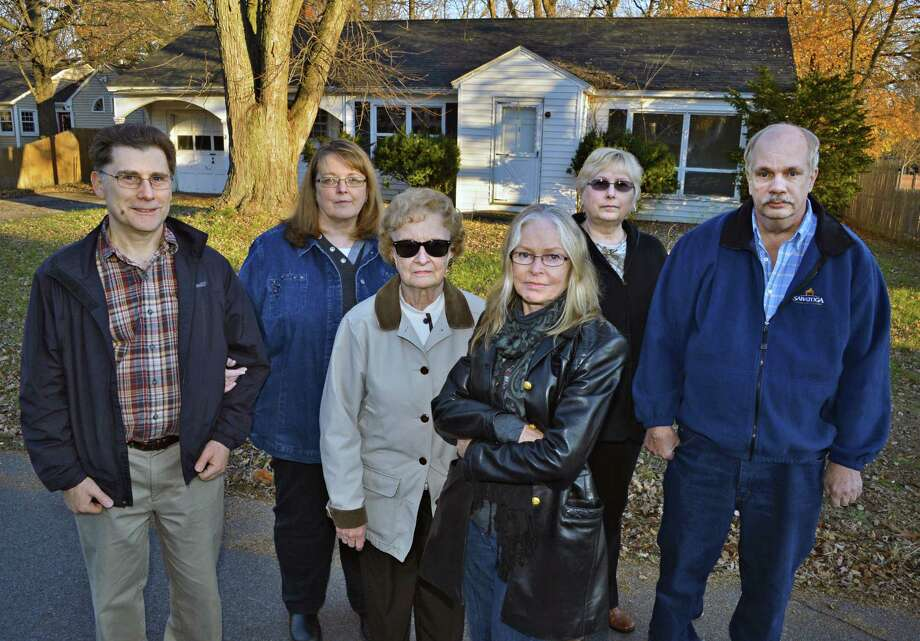 Neighbors, from left, Ron Barnard, Mary Lou Chaikowski, Lorraine Martin, Judi England, Joanne Cadalso and Stephen Cadalso in front of the vacant house at #1 Gabriel Terrace in Guilderland Wednesday Nov. 21, 2012.  (John Carl D'Annibale / Times Union) Photo: John Carl D'Annibale / 00020209A