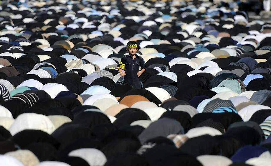 A Pakistani Shiite Muslim boy stands amongst worshippers as they offer noon prayers during a religious procession on the ninth day of holy month of Moharram in Karachi on November 24, 2012. The Pakistani Taliban on November 24 claimed responsibility for a bomb blast near a Shiite Muslim procession in northwest Pakistan that killed seven people. The blast went off as people from the minority Shiite Muslim community were gathering to mark the anniversary of the death of the Prophet Mohammed's grandson Imam Hussain in 680. ASIF HASSAN/AFP/Getty Images Photo: Asif Hassan, AFP/Getty Images