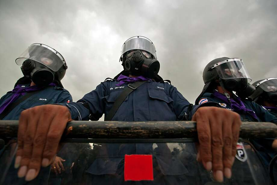 Thai riot policemen stand guard during a protest in Bangkok on November 24, 2012.  Thai police fired tear gas and detained dozens of people as tensions flared at an anti-government protest on November 24 in Bangkok, the scene of several outbreaks of violent unrest in recent years. JOAN MANUEL BALIELLAS/AFP/Getty Images Photo: Joan Manuel Baliellas, AFP/Getty Images