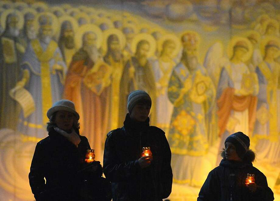 People carry candles in front of frescos in memory of the victims of the Holodomor famine in Kiev on November 24, 2012. Ukraine marked 80 years since the Stalin-era Holodomor famine, one of the darkest pages in its entire history that left millions dead and which is regarded by many as a genocide. The 1932-33 famine took place as harvests dwindled and Josef Stalin's Soviet police enforced the brutal policy of collectivising agriculture by requisitioning grain and other foodstuffs. SERGEI SUPINSKY/AFP/Getty Images Photo: Sergei Supinsky, AFP/Getty Images