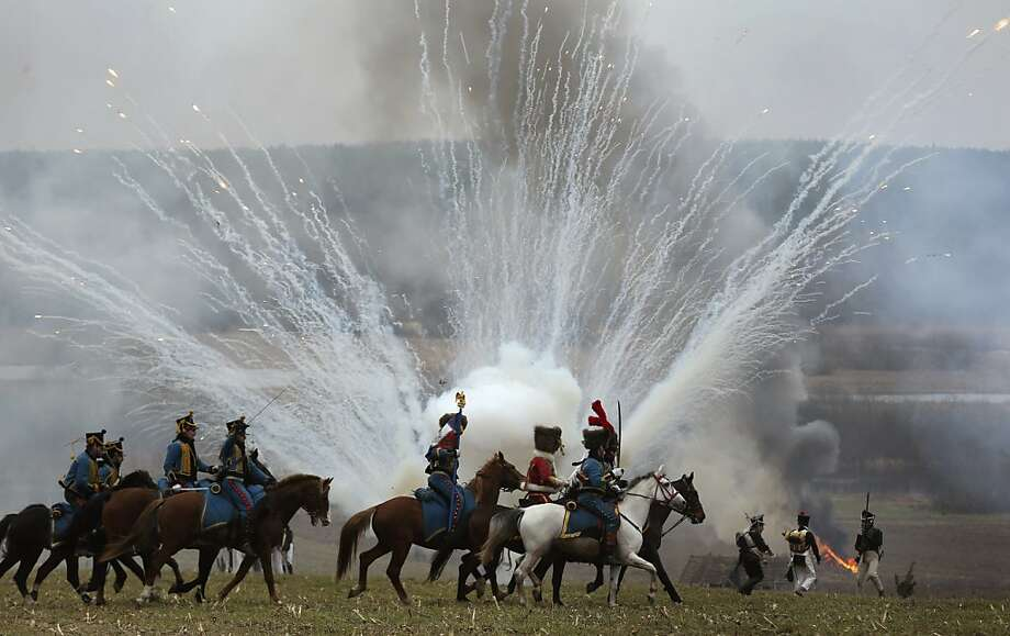 Men dressed as 1812-era Russian and French soldiers re-enact a staged battle near the Belarus village of Bryli, about 115 kilometers (70 miles) east of the capital, Minsk, Saturday, Nov. 24, 2012, to mark the 200th anniversary of the Berezina battle during Napoleon's army retreat from Russia. The retreat across the Berezina of the remnants of Napoleon's Grand Army, which invaded Russia June 24, 1812, took place from Nov. 26 to Nov. 29, 1812. About 50,000 people, soldiers from both sides and civilians, were killed during the crossing, which was effected under heavy Russian attack and saved Napoleon and his forces from capture. In total of nearly half a million soldiers, from France as well as all of the vassal states of Europe, who invaded Russia in June, barely 10,000 survived by the end of the campaign, December 1812. (AP Photo/Sergei Grits) Photo: Sergei Grits, Associated Press