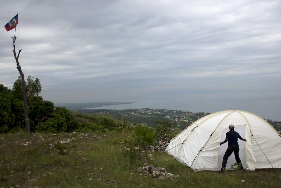 A veteran of Haiti's former army zips his tent closed where informal military training for recruits is taking place on a hillside clearing in the beach resort town of Mariani, Haiti, Saturday, Nov. 24,  2012.  The leaders of a ragtag group of ex-soldiers that called for the return of Haiti's disbanded armed forces earlier this year renewed their call Saturday following six months in hiding. (AP Photo/Dieu Nalio Chery) Photo: Dieu Nalio Chery, Associated Press
