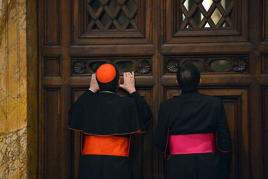 Italian cardinal Giuseppe Betori (L) and a bishop take a glimpse through a door during the courtesy visit to the cardinals on November 24, 2012 at the Apostolico palace at the Vatican. Six non-European prelates are set to join the Catholic Church's College of Cardinals, a move welcomed by critics concerned that the body which will elect the future pope is too Eurocentric. VINCENZO PINTO/AFP/Getty Images Photo: Vincenzo Pinto, AFP/Getty Images