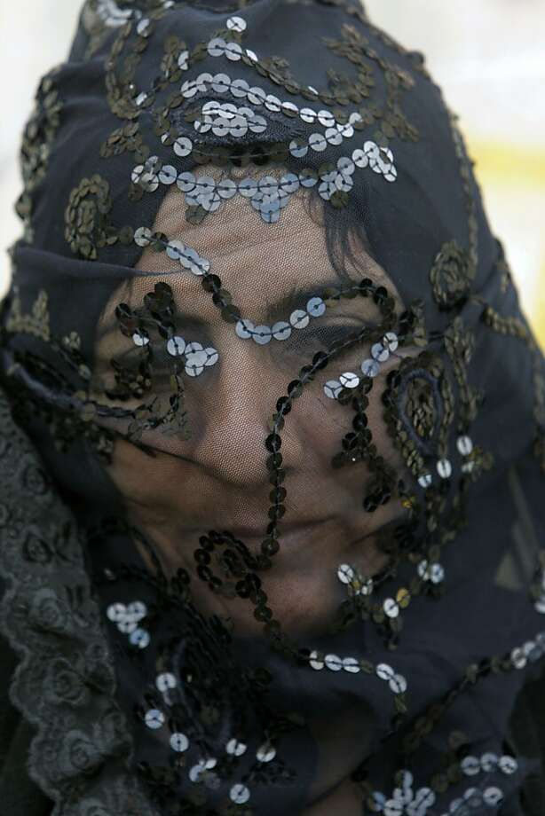 An Iranian woman covers her face symbolically, as she takes part in a mourning ceremony in the city of Khorramabad, southwest of the capital Tehran, Iran, Saturday, Nov. 24, 2012, for Ashoura, marking the death anniversary of Imam Hussein, the grandson of Islam's Prophet Muhammad. Hussein, one of Shiite Islam's most beloved saints, was killed in a 7th century battle at Karbala, Iraq. The ceremony depicts a part of the legend of Imam Hussein's family after being detained by their enemies, and taking them to then capital of Islamic world, Damascus, through forty stations on the road. (AP Photo/Vahid Salemi) Photo: Vahid Salemi, Associated Press