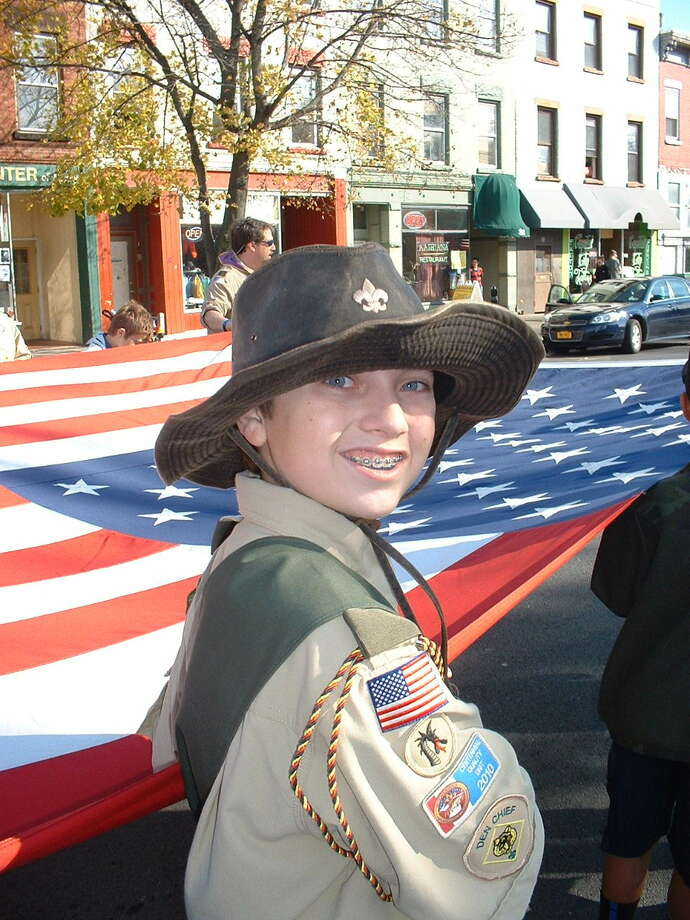 Caleb Czolowski marches in the Veterans Day Parade holding the large flag with troop #62 The photo was taken at the Veterans Day Parade 11/12/12 in Albany. He was marching with the Elks and  Boy Scout troop #62 out of Latham, they were holding a mini Garrison flag (on a windy day this was very hard!)   He is very involved with the Boy Scouts and this was his first parade. (Laura Czolowski)
