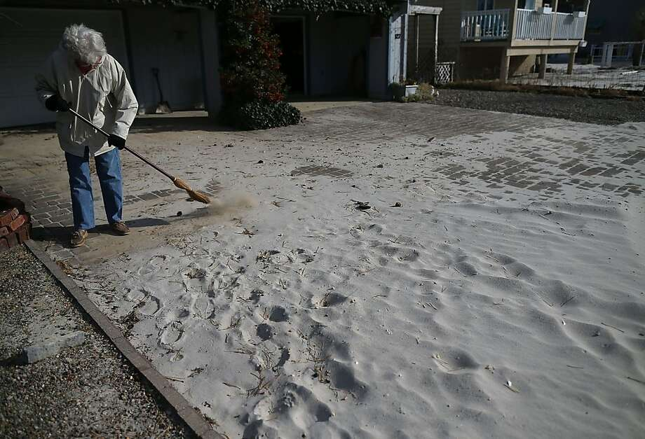 Sue Vehslage sweeps sand off her driveway that was washed in by Superstorm Sandy, on November 24, 2012 in Long Beach Island, New Jersey. New Jersey Gov. Christie estimated that Superstorm Sandy will cost New Jersey $29.4 billion in damage and economic losses.  (Photo by Mark Wilson/Getty Images) Photo: Mark Wilson, Getty Images