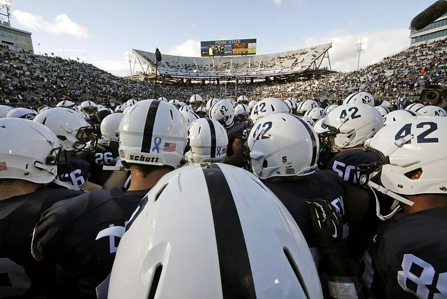 Penn State football players huddle on the field during warm ups before an NCAA college football game against Wisconsin in State College, Pa., Saturday, Nov. 24, 2012. The 42 worn on the left side of their normally white helmets is in honor of injured senior linebacker Michael Mautii, who wears No. 42. (AP Photo/Gene J. Puskar) Photo: Gene J. Puskar, Associated Press