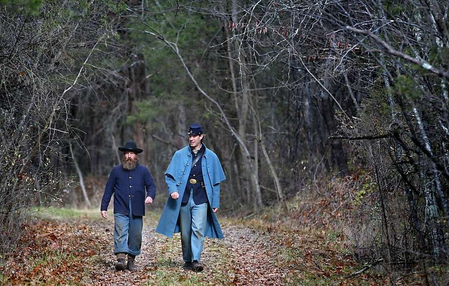 Union Army re-enactors Fred Rickard of Frederick County, Va., left, and Sam Cathey of Hagerstown, Md., both with the 22nd Iowa 19th Corps, walk to their cars on the Cedar Creek Battlefield in Middletown Va. Saturday, Nov. 24, 2012. The pair were retrieving an axe and hatchet to clear brush from their encampment while participating in a 10th anniversary event to mark the battlefield becoming a National Historical Park. (AP Photo, The Winchester Star, Jeff Taylor) Photo: Associated Press