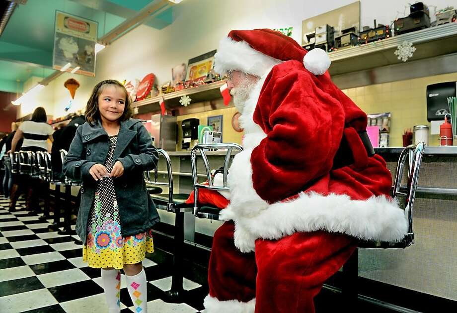 Jalyn Arnold, 7, talks with Santa at the 5th Street Diner in downtown Great Falls, Mont., on Saturday, Nov. 24, 2012. Downtown Great Falls was busy with shoppers Saturday morning as the Small Business Saturday campaign continued for a third year, encouraging shoppers to support their downtown's small businesses. (AP Photo/The Great Falls Tribune, Rion Sanders)  Photo: Rion Sanders, Associated Press