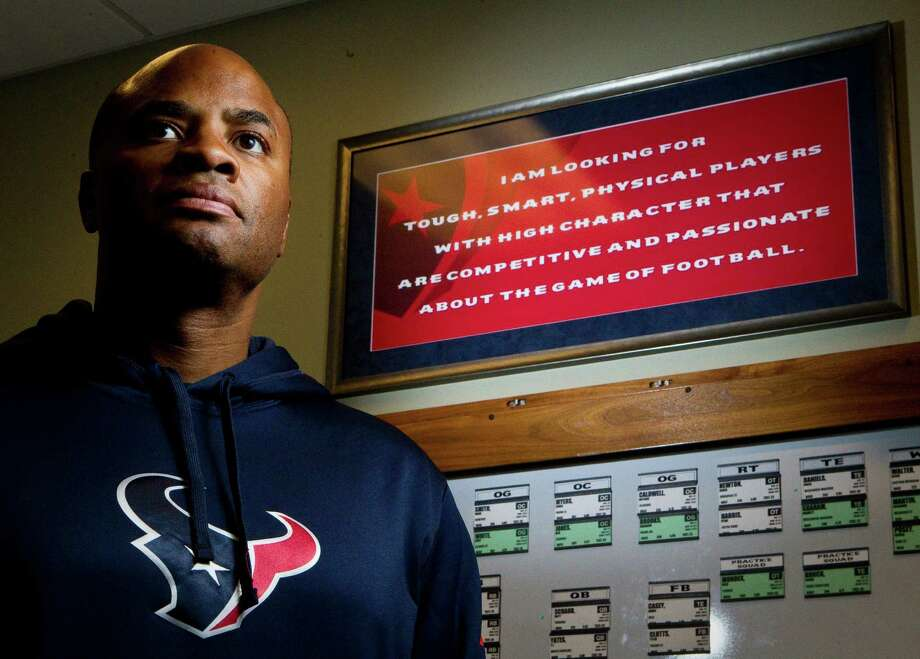 "General manager Rick Smith stands by a sign in his office that, in part, stresses ""high character"" as a key part of a player's makeup. Photo: Nick De La Torre, Staff / © 2012  Houston Chronicle"