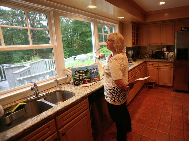 Gail Newell, of New York City, checks out the kitchen view while house hunting in Weston on Thursday, October 4, 2012. Newell, who has a daughter, would like to move to Weston for the town's top quality school system. Photo: Brian A. Pounds / Connecticut Post