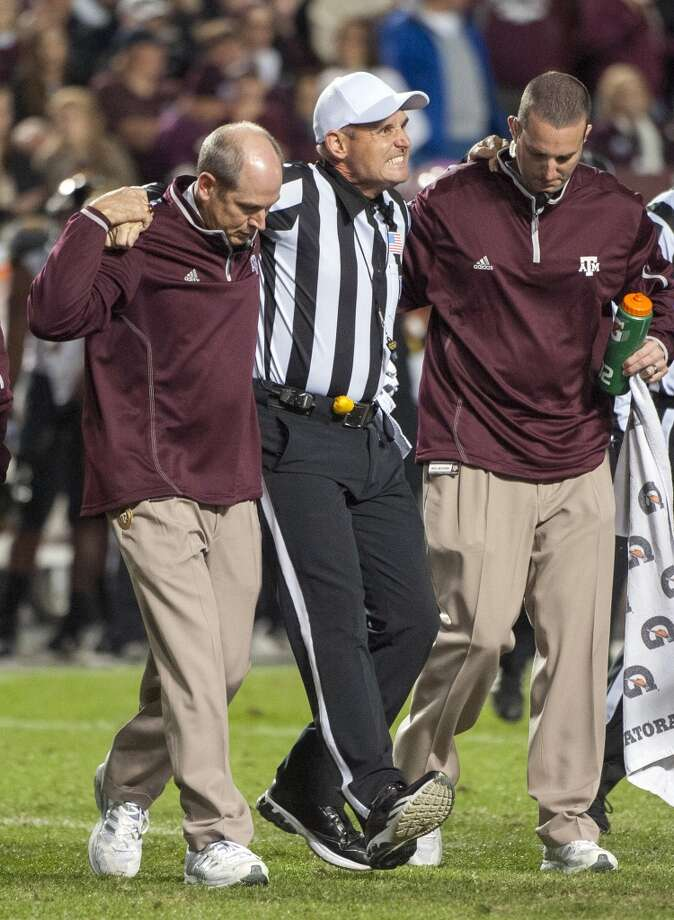 Referee Matt Loeffler, center, is helped off the field by Texas A&M staff after being injured during the second quarter of an NCAA college football game against Missouri, Saturday, Nov. 24, 2012, in College Station, Texas.  (Dave Einsel / Associated Press)