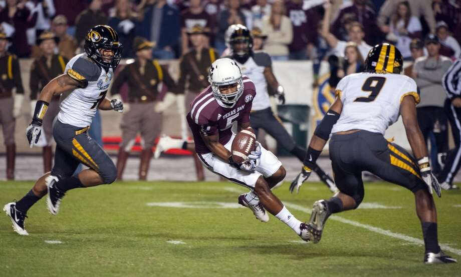 Texas A&M's Kenric McNeil (5) makes a catch between Missouri's Randy Ponder, left, and Braylon Webb (9) during the first quarter of an NCAA college football game on Saturday, Nov. 24, 2012, in College Station, Texas.  (Dave Einsel / Associated Press)