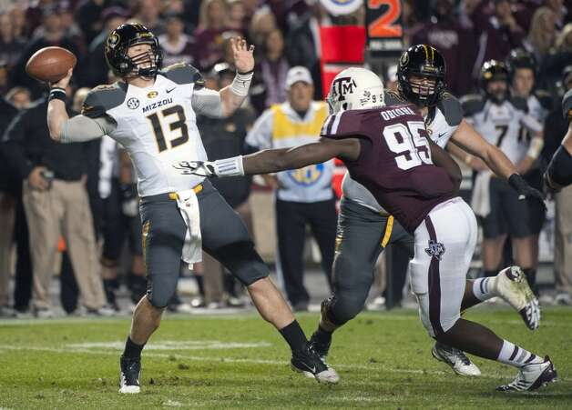 Missouri quarterback Corbin Berkstresser (13) passes under pressure by Texas A&M's Julien Obioha (95) during the second quarter of an NCAA college football game on Saturday, Nov. 24, 2012, in College Station, Texas.  (Dave Einsel / Associated Press)