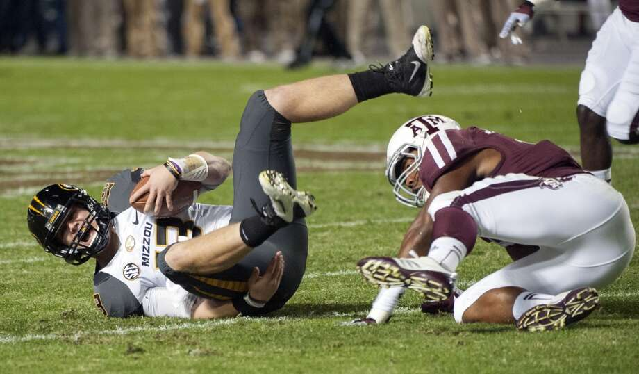 Missouri quarterback Corbin Berkstresser, left, hits the ground after being sacked by Texas A&M's Jonathan Stewart, right, during the first quarter of an NCAA college football game on Saturday, Nov. 24, 2012, in College Station, Texas.  (Dave Einsel / Associated Press)