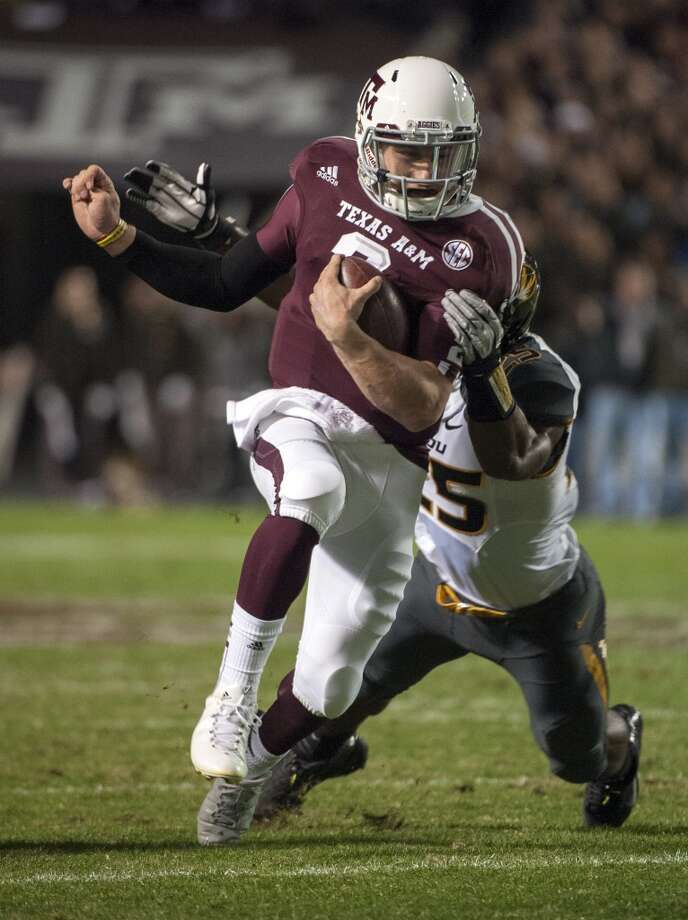 Texas A&M's Johnny Manziel, front, runs through Missouri's Zaviar Gooden (25) during the first quarter of an NCAA college football game on Saturday, Nov. 24, 2012, in College Station, Texas. (Dave Einsel / Associated Press)