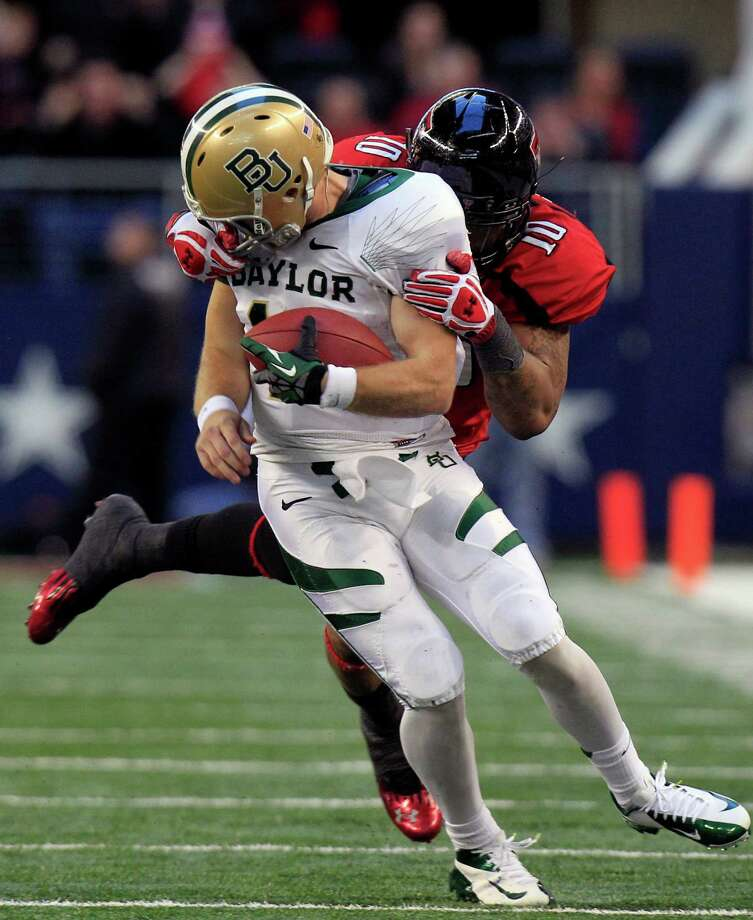 Baylor quarterback Nick Florence, who threw for 396 yards and ran for 51, is the victim of a face mask penalty by Tech's Pete Robertson. Photo: LM Otero, STF / AP