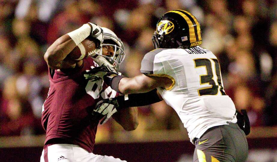 Texas A&M wide receiver Malcome Kennedy (84) is hit hard by Missouri defensive back E.J. Gaines (31)