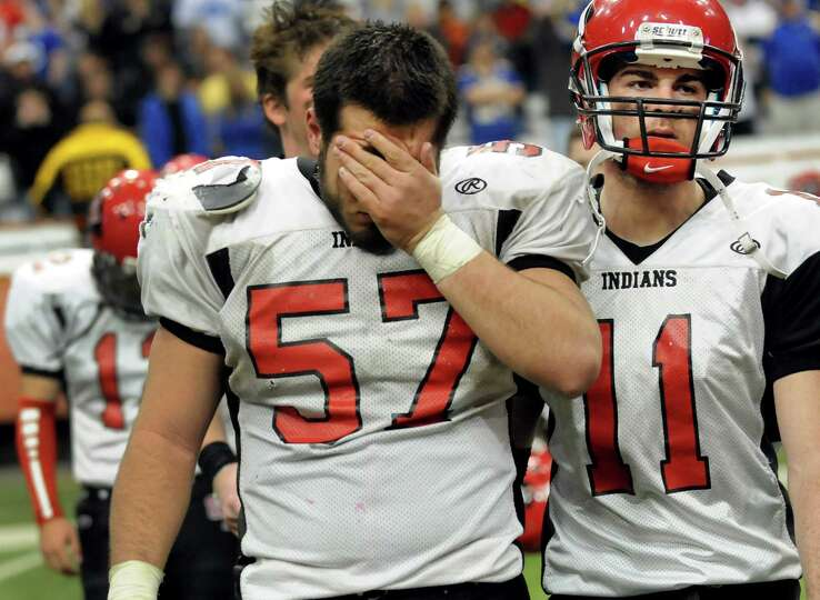 Glens Falls' Lee Girard (57), left, and his cousin Cam Girard (11) react to their 42-12 loss to Main