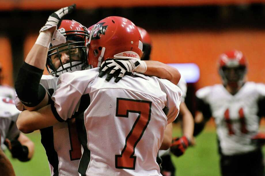Glens Falls' Matt Girard (19), left, embraces Zach Infield (7) when he scores a touch down during their Class B football state final against  Maine-Endwell on Saturday, Nov. 24, 2012, at the Carrier Dome in Syracuse, N.Y. (Cindy Schultz / Times Union) Photo: Cindy Schultz / 00020205A
