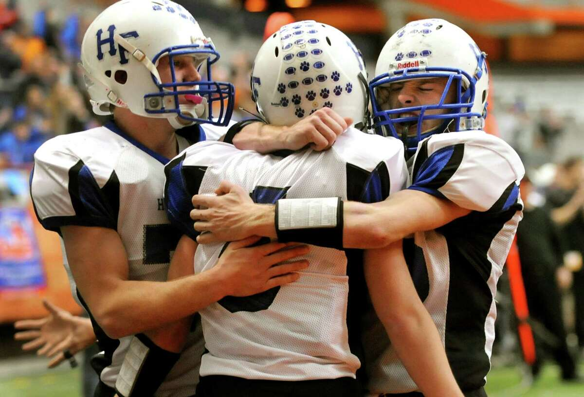 Hoosick Falls' Josh Brogue (5), center, celebrates his touchdown with teammates Derek Bird (77), left, and Grady Beck (75) during their Class C football state final against Hornell on Saturday, Nov. 24, 2012, at the Carrier Dome in Syracuse, N.Y. Hoosick Falls wins 34-21. (Cindy Schultz / Times Union)