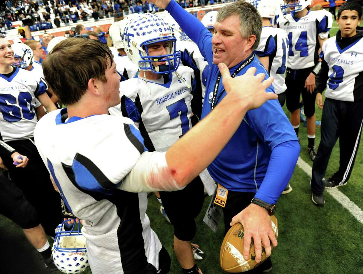 Hoosick Falls' coach Ron Jones, right, celebrates with players Billy Pine(4), left, and Randy Tutunjian (7), center, when they win 34-21 over Hornell in the Class C football state final on Saturday, Nov. 24, 2012, at the Carrier Dome in Syracuse, N.Y. (Cindy Schultz / Times Union)