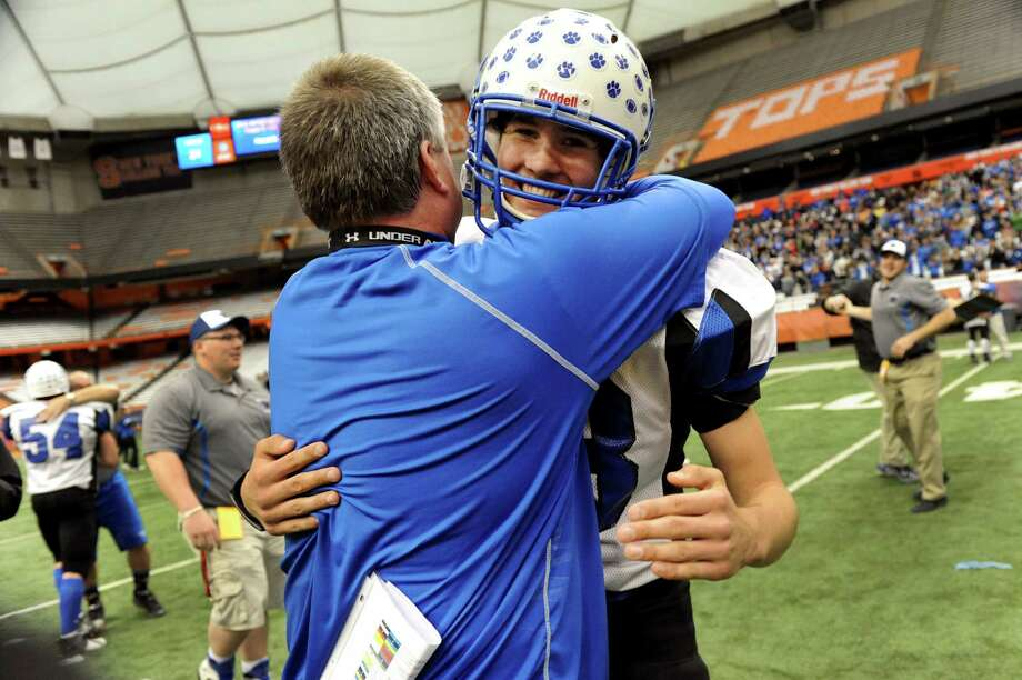 Hoosick Falls' coach Ron Jones, right, embraces Matt Brewster (83) when they win 34-21 over Hornell in the Class C football state final on Saturday, Nov. 24, 2012, at the Carrier Dome in Syracuse, N.Y. (Cindy Schultz / Times Union) Photo: Cindy Schultz / 00020204A