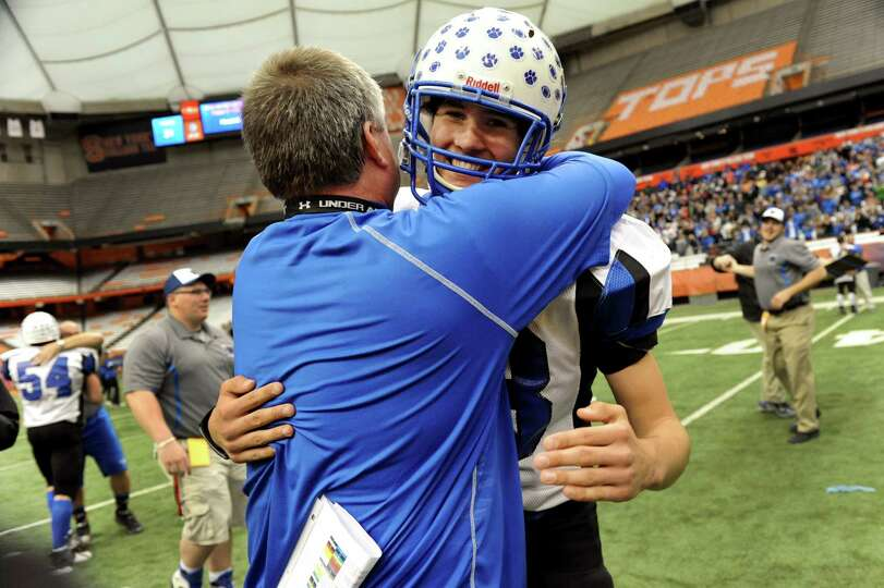 Hoosick Falls' coach Ron Jones, right, embraces Matt Brewster (83) when they win 34-21 over Hornell