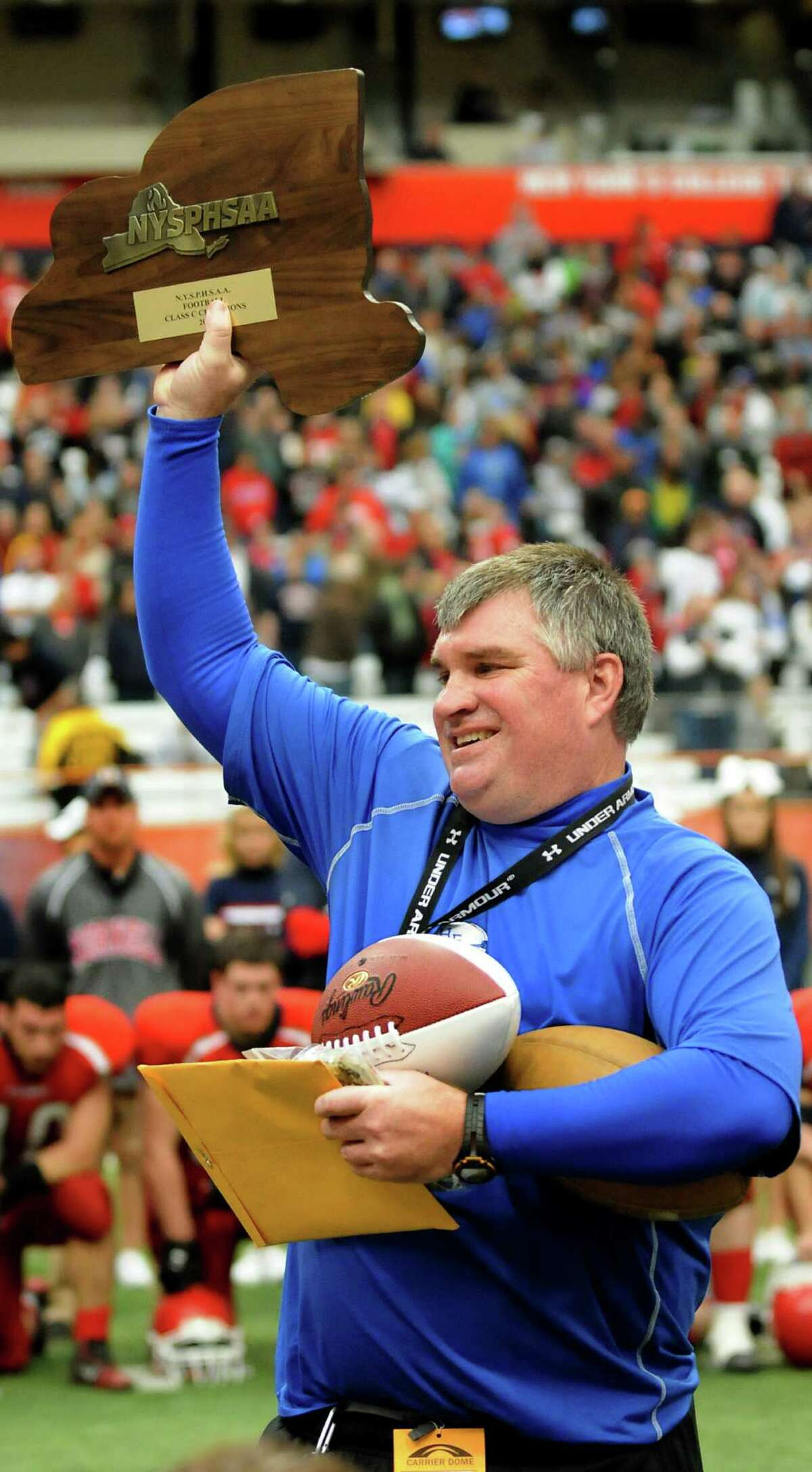 Hoosick Falls' coach Ron Jones holds up the state title when his team wins 34-21 over Hornell in the Class C football state final on Saturday, Nov. 24, 2012, at the Carrier Dome in Syracuse, N.Y. (Cindy Schultz / Times Union)