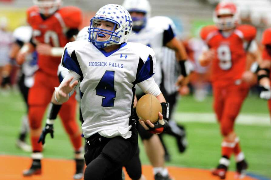 Hoosick Falls' quarterback Billy Pine (4), center, gains yards during the Class C football state fin