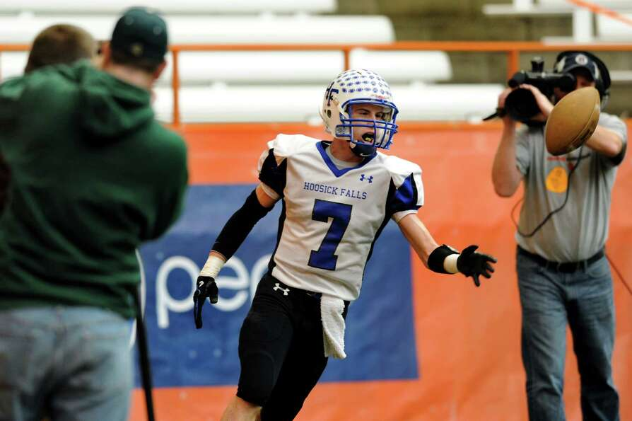 Hoosick Falls' Randy Tutunjian (7), center, flips the ball to an official after making a touch down