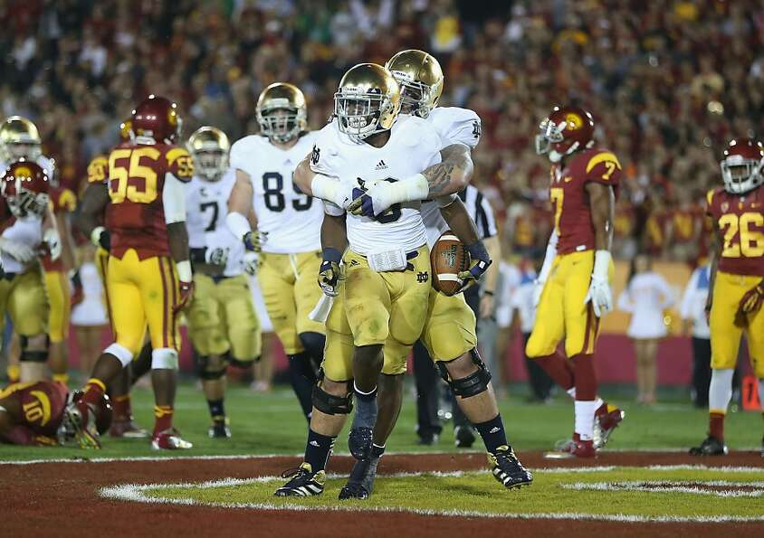 Notre Dame's Braxston Cave gives Theo Riddick (6) a hug after Riddick's 9-yard touchdown run.