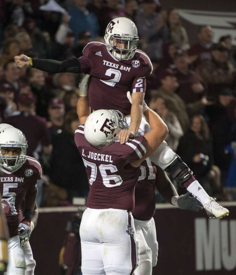 Texas A&M quarterback Johnny Manziel (2) gets a lift from Luke Joeckel (76) after running 18-yards for a touchdown during the third quarter of an NCAA college football game against Missouri, Saturday, Nov. 24, 2012, in College Station, Texas.  (Dave Einsel / Associated Press)