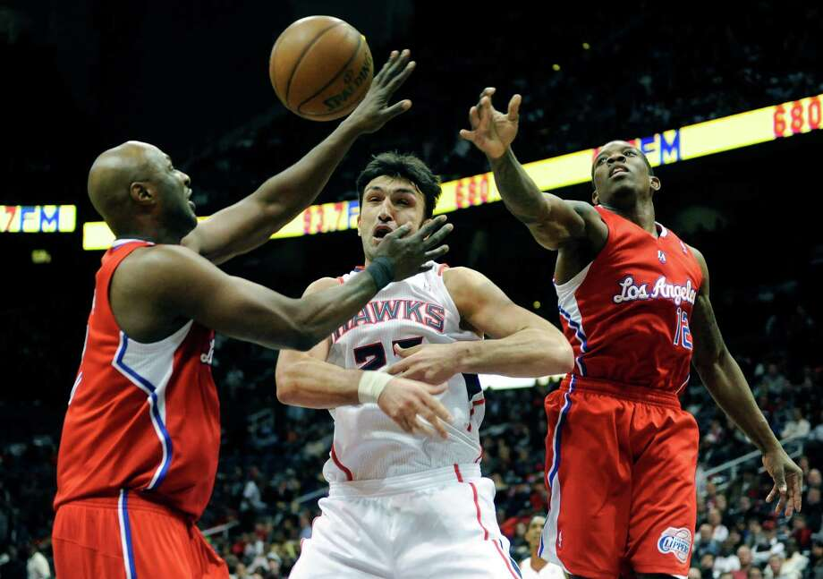 Los Angeles Clippers' Lamar Odom (7) and Eric Bledsoe (12) cover Atlanta Hawks' Zaza Pachulia in the first half of an NBA basketball game at Philips Arena in Atlanta, Saturday, Nov. 24, 2012. (AP Photo/David Tulis) Photo: Dave Tulis