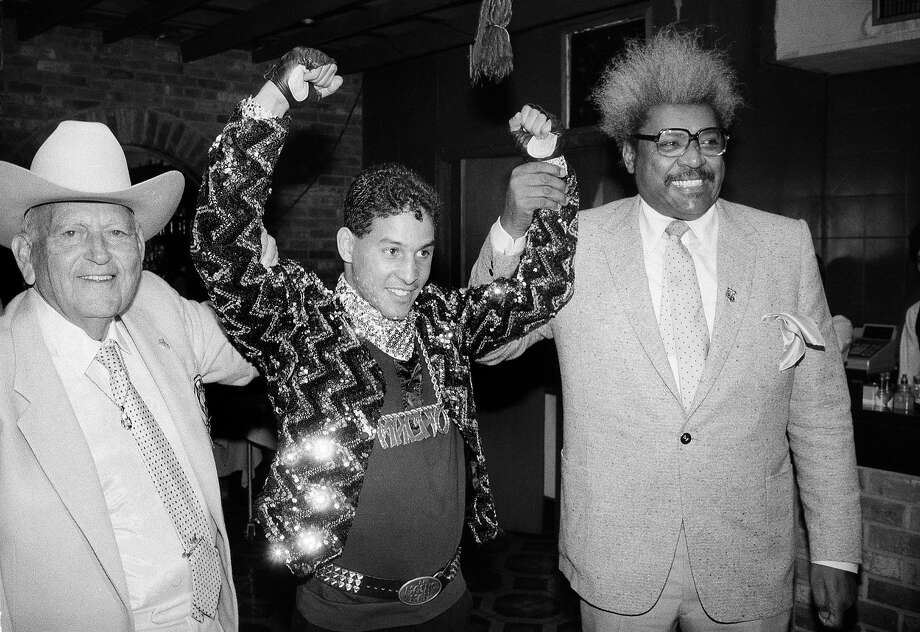 "In this Dec. 9, 1986 file photo, Hector ""Macho"" Camacho WBC lightweight boxing champion, is escorted by Marty Cohen, left, and boxing promoter Don King, right, during a news conference in New York.  Famed Puerto Rican boxer Camacho is clinically brain dead, doctors said Thursday, Nov. 22, 2012, though they said family members were disagreeing on whether to take him off life support.  Dr. Ernesto Torres said doctors have finished performing all medical tests on Camacho, who was shot in the face Tuesday night. (AP Photo/David Bookstaver, File) Photo: David Booksatver, Associated Press"