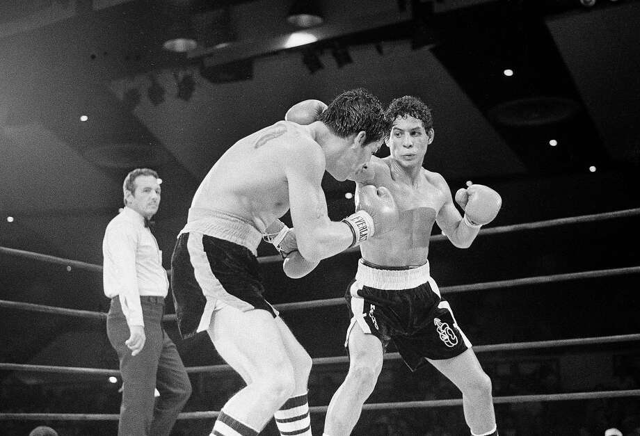 "In this July 11, 1982 file photo, Luis Loy Jr., left, ducks under a blow by Hector Camacho early in a scheduled 10-round junior lightweight boxing bout at Felt Forum in New York. Hector ""Macho"" Camacho, a boxer known for skill and flamboyance in the ring, as well as for a messy personal life and run-ins with the police, has died, Saturday, Nov. 24, 2012, after being taken off life support. He was 50. (AP Photo/Elias, File) Photo: Elias, Associated Press"