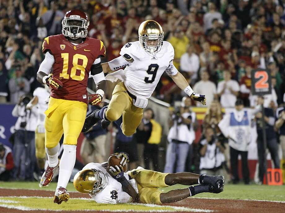 Notre Dame wide receiver Robby Toma, top, jumps onto running back Theo Riddick, bottom, to celebrate after Riddick dove into the end zone for a touchdown, as Southern California linebacker Dion Bailey, left, runs past eduring the first half of an NCAA college football game, Saturday, Nov. 24, 2012, in Los Angeles. (AP Photo/Danny Moloshok) Photo: Danny Moloshok, Associated Press