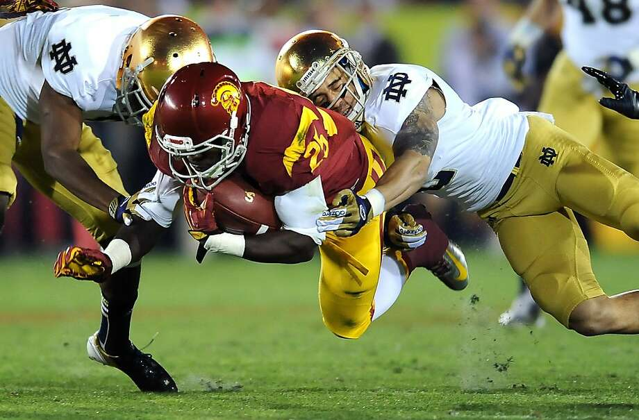 USC running back Silas Redd is brought down by Notre Dame's KeiVarae Russell, left, and Bennett Jackson in the second quarter at the Los Angeles Coliseum on Saturday, November 24, 2012, in Los Angeles, California. (Wally Skalij/Los Angeles Times/MCT) Photo: Wally Skalij, McClatchy-Tribune News Service