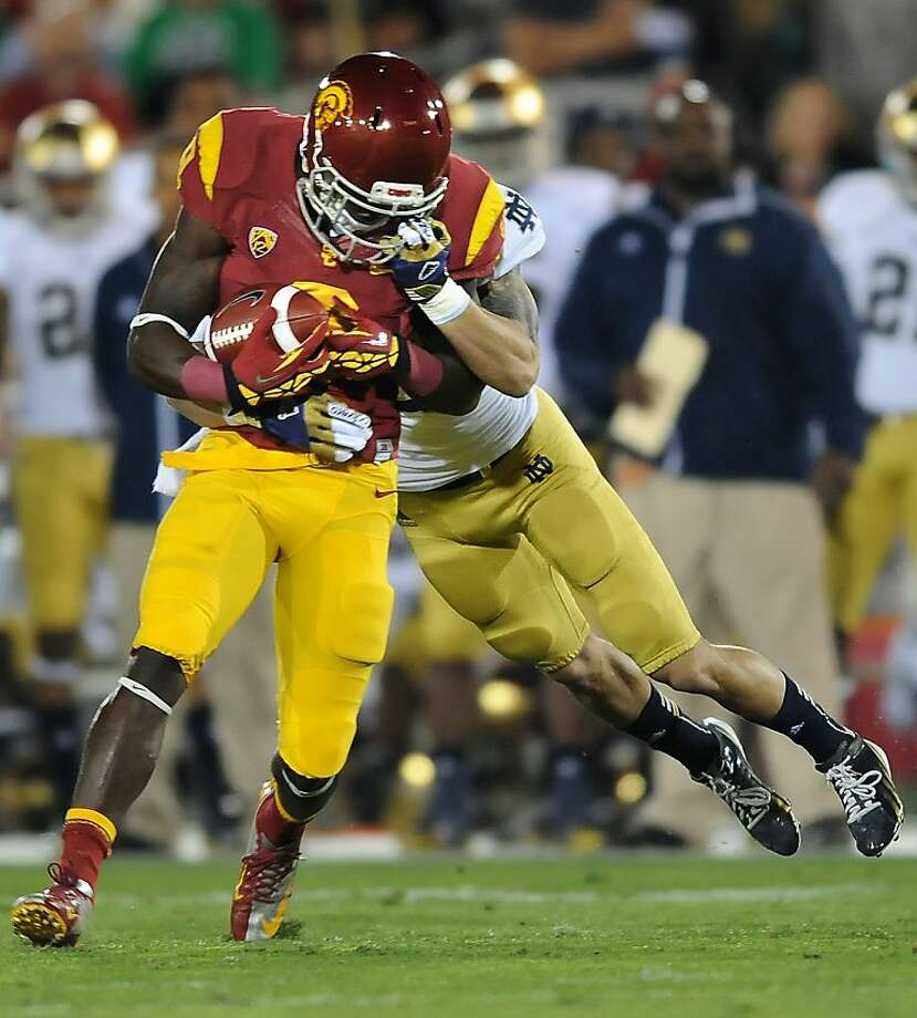 Notre Dame's Bennett Jackson grabs the face mask of USC receiver Marquise Lee, drawing a penalty, on a tackle in the first quarter at the Los Angeles Coliseum on Saturday, November 24, 2012, in Los Angeles, California. (Wally Skalij/Los Angeles Times/MCT) Photo: Wally Skalij, McClatchy-Tribune News Service